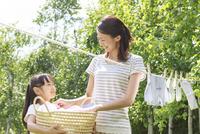 新緑の中、洗濯物を干す母子