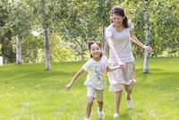新緑の中、手をつないで走る母子
