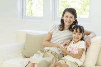 ソファーでスマートフォンを操作する母子