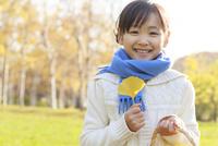 紅葉の中、落ち葉を持つ6歳の女の子 10208001888| 写真素材・ストックフォト・画像・イラスト素材|アマナイメージズ