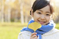 紅葉の中、落ち葉を持つ6歳の女の子