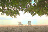 夕焼けに染まり始めたビーチに置かれたペアのイス