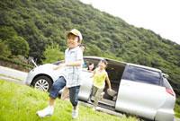 車から草原に向かって走る子ども
