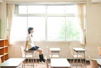 机に座る女子高校生
