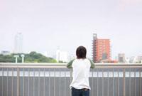屋上で遠くを見る大学生