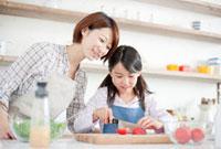 トマトを切っている女の子と見ている母親