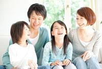 窓際に座り笑い合っている家族四人
