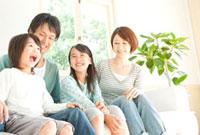 男性の前に座り大きな口を開ける男の子と笑顔の母親と女の子