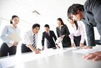 資料をテーブルに広げ会議をする男女のビジネスマン