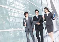 歩きながら会議資料に目を通す男女のビジネスマン
