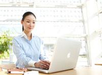 明るいテーブル席でパソコンで作業する女性ビジネスマン