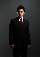 黒バックの前に立つ男性ビジネスマンのポートレート 10230002286| 写真素材・ストックフォト・画像・イラスト素材|アマナイメージズ
