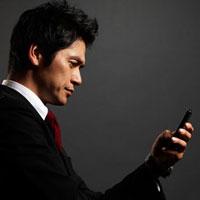 黒バックの前に携帯電話を手に持つ男性ビジネスマンの横顔