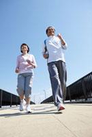 青空の歩道を笑顔でジョギングしているシニア夫婦