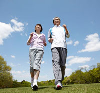 青空の芝生の上を笑顔でジョギングしているシニア夫婦