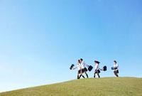 青空の下の芝の高台を仲良く楽しそうに歩く女子高生四人