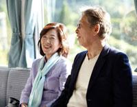 山間の田舎町を電車で旅行する笑顔のシニア夫婦