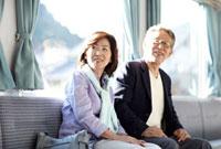 山間の田舎町を電車で旅行するシニア夫婦