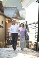 白い土壁と石畳の小道を腕を組んで歩くシニア夫婦 10230002637| 写真素材・ストックフォト・画像・イラスト素材|アマナイメージズ