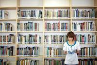 図書館の本棚の前で本を読む女子大生