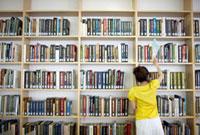 大学の図書館の本棚から本を選んでいる女子大生