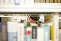 本棚越しに見える本を選んでいる女子大生の目元