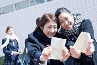 合格発表ボードの前で受験票を差し出す笑顔の女子高生二人