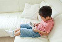 携帯ゲーム機で遊ぶ男の子