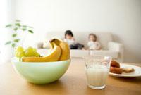 テーブルの果物とソファの子供