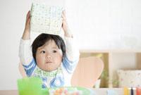 プレゼントを上に上げる子供 10236000510| 写真素材・ストックフォト・画像・イラスト素材|アマナイメージズ