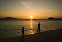 夕日時の砂浜を歩く親子