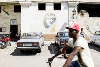 キューバ ハバナ市内のチェゲバラの壁画と自転車を運転する人