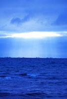 朝の光芒と漁船