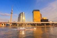 東京スカイツリーとビルに反射する夕日と水上バス 10247003797| 写真素材・ストックフォト・画像・イラスト素材|アマナイメージズ