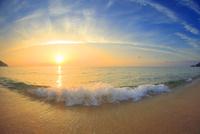 渚に寄せる波と夕日