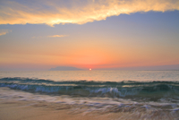 渚に寄せる波と夕日と口永良部島