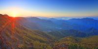 カラマツ林の紅葉と富士山などの山並みと朝日