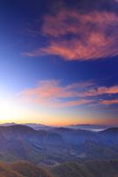 カラマツ林の紅葉と富士山などの山並みと朝焼け