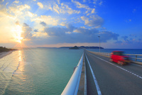 角島大橋を走行する赤い自動車と夕日と海