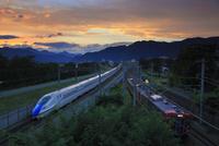 北陸新幹線E7系としなの鉄道の電車と夕焼け