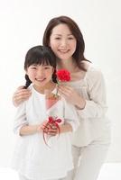 赤いカーネーションを持つ女の子と母