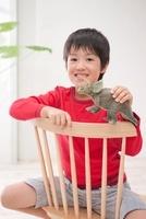 玩具の恐竜を持って椅子に座っている男の子