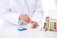 リトマス試験紙と乳鉢と乳棒で薬剤を混ぜる手