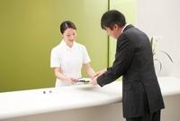 病院の受付で受診受付をする女性事務員とビジネスマン 10248004763| 写真素材・ストックフォト・画像・イラスト素材|アマナイメージズ