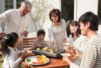 家の庭で焼肉を食べる3世代家族