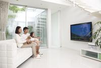 リビングでテレビをみる家族と犬