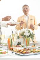 シャンパンと料理を楽しむホームパーティーの人達