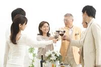赤ワインで乾杯する中高年夫婦とホームパーティーのお客様