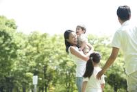 芝生の公園で遊ぶ四人家族