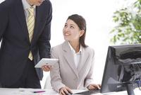デスクワーク中のOLにPCを見せるビジネスマン 10248012528| 写真素材・ストックフォト・画像・イラスト素材|アマナイメージズ